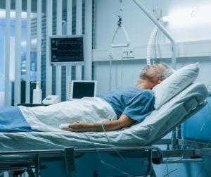 meżczyzna leżący w łózku szpitalnym